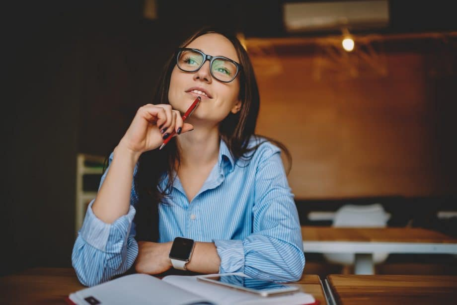 Professional woman in a coffee shop setting looking up appearing to be thinking about something intently.